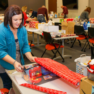 Ash Brokerage Impact Committee Wrap Presents for Christmas Families